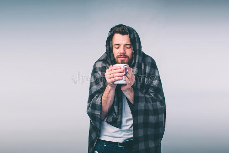 Обернутый в теплых одеяле или шотландке, больной, молодой snotty человек в стеклах выпивая теплый заживление чай стоковое изображение