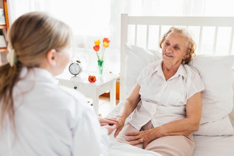 Обеспечивать заботу для пожилых людей Доктор навещая пожилой пациент дома стоковые изображения