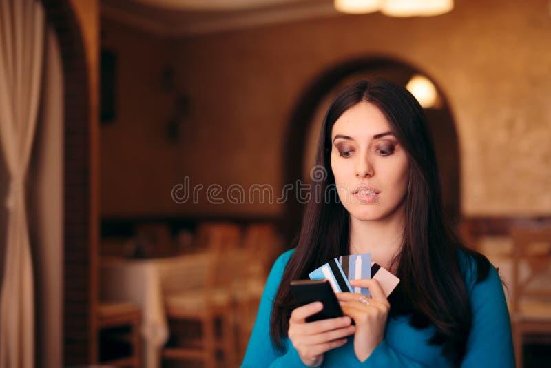 Обеспокоеная женщина держа множественные кредитные карточки и смартфон стоковое фото
