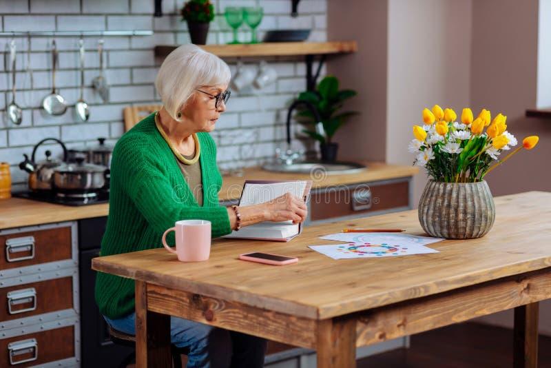 Обеспокоеная седая женщина в стеклах поворачивая страницы книги рецепта стоковое фото