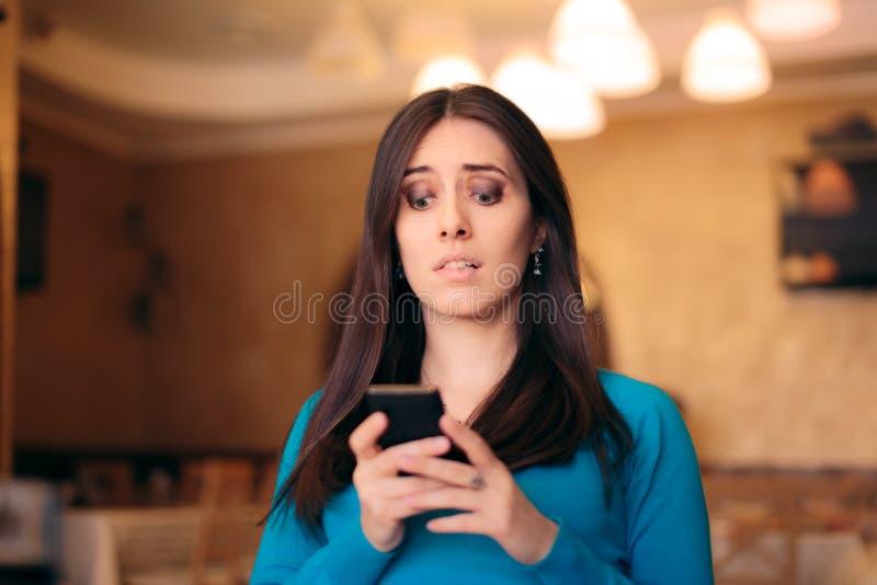 Обеспокоенные текстовые сообщения чтения женщины в ресторане стоковые фотографии rf