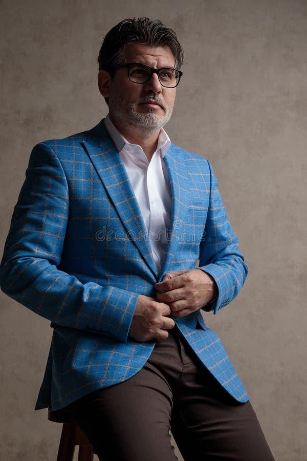 Обеспокоенный бизнесмен регулируя его куртку и смотря к стороне стоковые фото