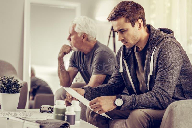Обеспокоеный сын рассматривая медицинскую оценку его седого отца стоковая фотография