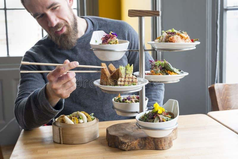 Обедать клиент принимает тофу используя палочки от Tiered сервера стоковые фото
