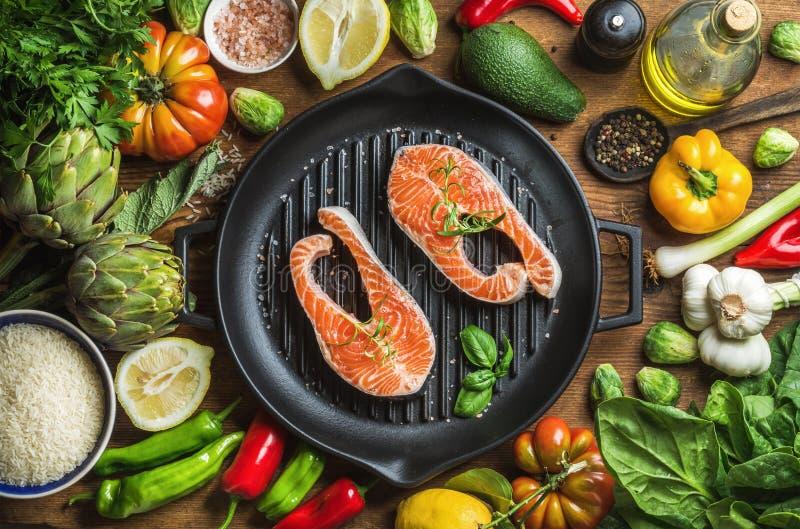 Обедающий варя ingredints Сырцовые сырые salmon рыбы с овощами, рисом, травами, специями и маслом в железном лотке приготовления  стоковое фото rf