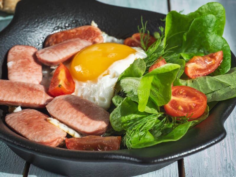Обильный завтрак взбитых яя с сосисками, томатами вишни и салатом лист на черном круглом лотке Подача на поднос доски стоковые фото