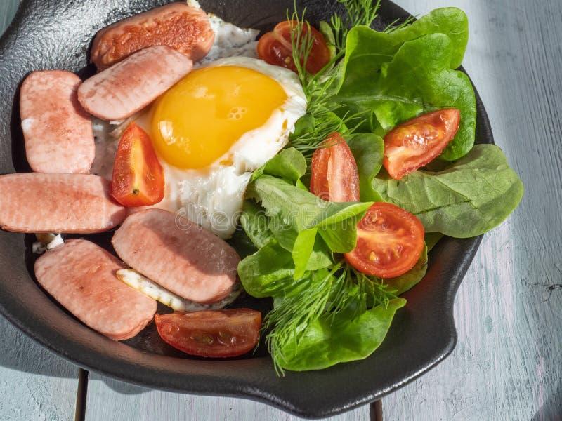 Обильный завтрак взбитых яя с сосисками, томатами вишни и салатом лист на черном круглом лотке Подача на деревянную планку стоковая фотография rf