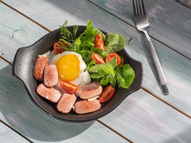 Обильный завтрак взбитых яя с сосисками, томатами вишни и салатом лист на черном круглом лотке Подача на поднос доски стоковые фотографии rf
