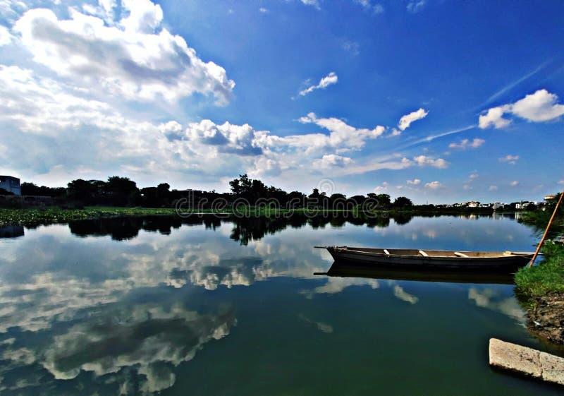 облака деревьев природы шлюпки вида на озеро красочные стоковое фото