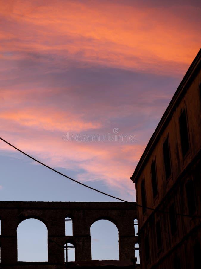 Облака захода солнца в старой части городка - получившегося отказ здания и старого римского акведука на заднем плане стоковое изображение