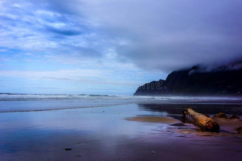 Облака зимы над заревом захода солнца океана на пляже стоковое изображение