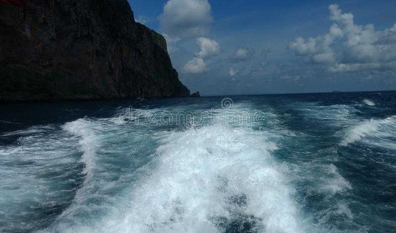 Облака на голубом небе с океанскими волнами и горой, обоями предпосылки стоковое фото