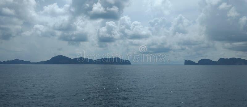 Облака на голубом небе с океанскими волнами и горой, обоями предпосылки стоковая фотография rf