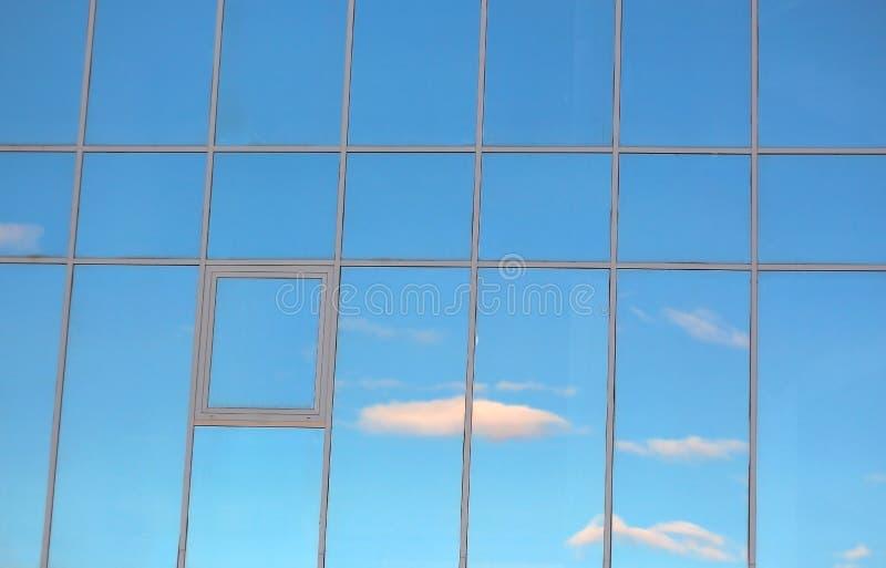 Облака отраженные в окнах современного офисного здания стоковые фото