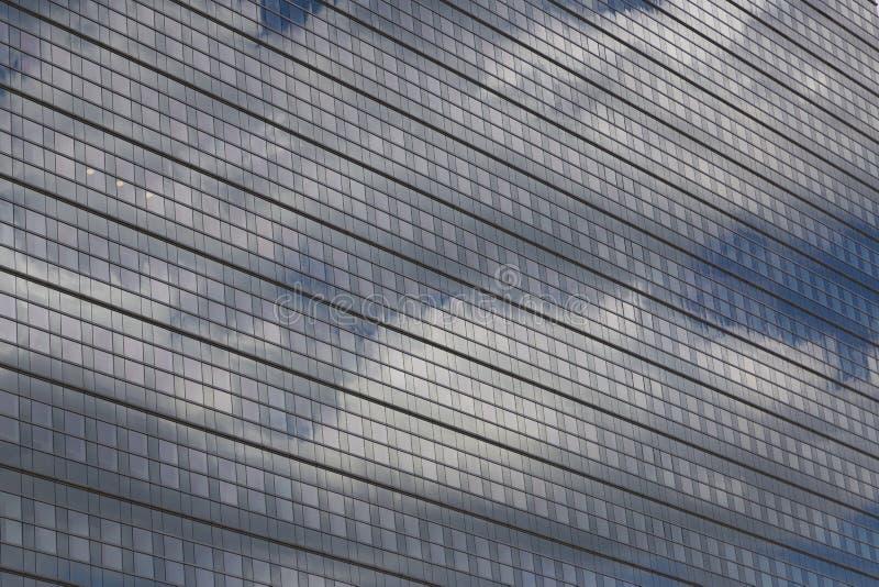 Облака отражены на стеклянном фасаде дома стоковые фото