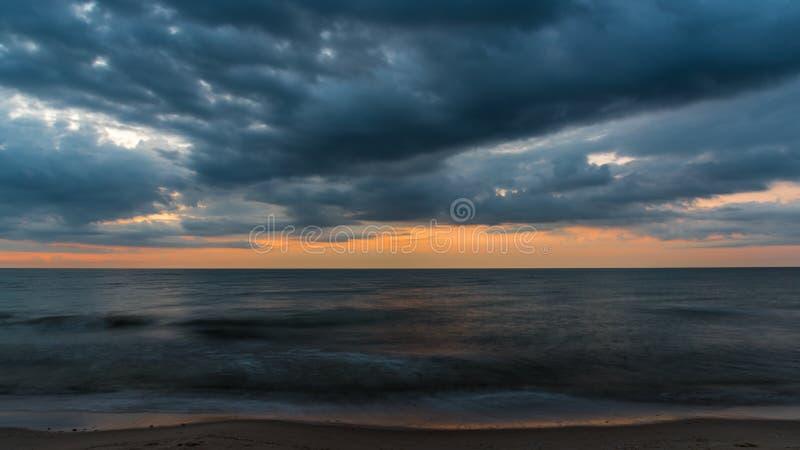 Облака покрывают море в вечере стоковая фотография rf
