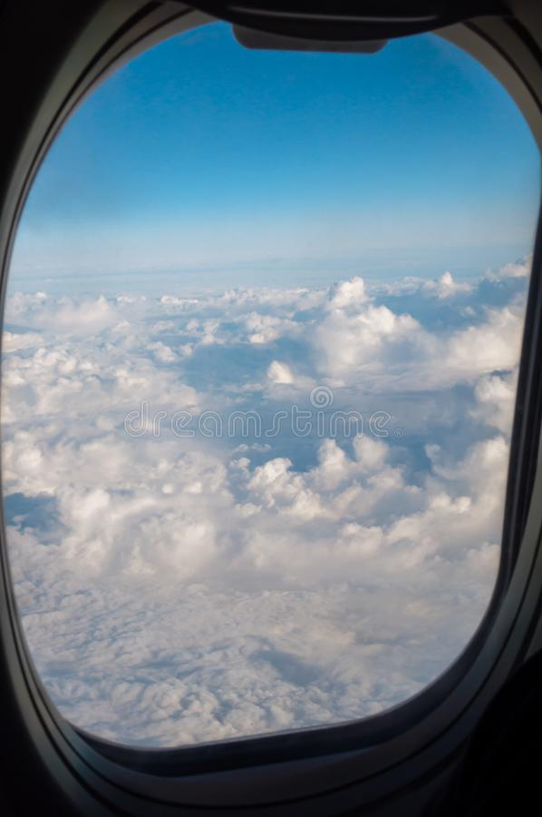 Облака через иллюминатор самолета стоковые фотографии rf