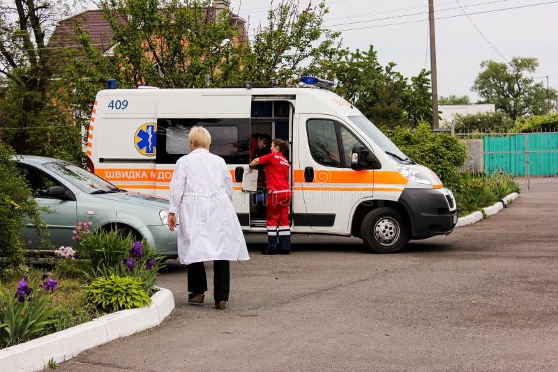 ОБЛАСТЬ КИЕВА, УКРАИНА - 12-ое мая 2016: машина скорой помощи и медсестра на улице Машина скорой помощи около больницы стоковая фотография rf