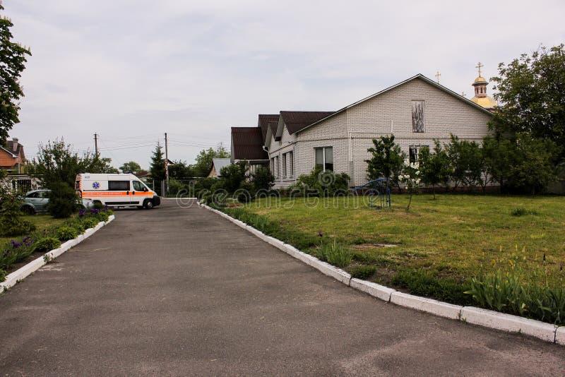 ОБЛАСТЬ КИЕВА, УКРАИНА - 12-ое мая 2016: машина скорой помощи и медсестра на улице Машина скорой помощи около больницы стоковое изображение rf