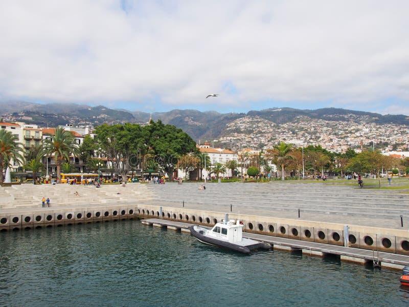 Область портового района гавани Фуншала со шлюпкой береговой охраны причаленной в людях дока сидела на конкретных шагах с городом стоковые изображения