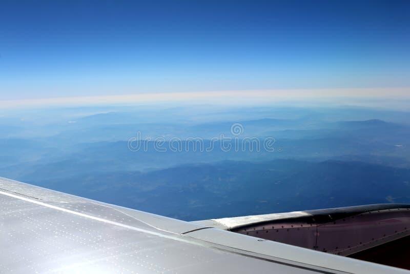 Облачное небо под крылом самолета стоковые изображения
