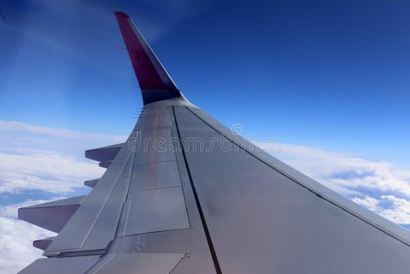 Облачное небо под крылом самолета стоковая фотография