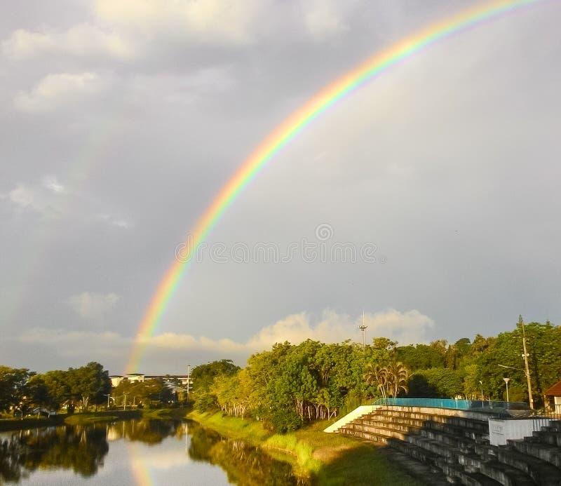 Облачное небо с радугой после дождя стоковые изображения rf