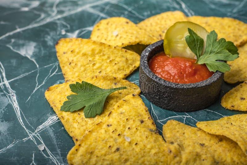 Обломоки мозоли Tortilla или Nachos с соусом в черном шаре, на красивой, голубой предпосылке стоковое фото rf