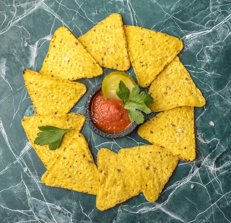 Обломоки мозоли Tortilla или Nachos с соусом в черном шаре, на красивой, голубой предпосылке над взглядом стоковое фото