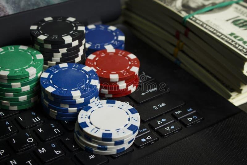 Обломоки покера и пакеты долларов на ноутбуке стоковая фотография rf