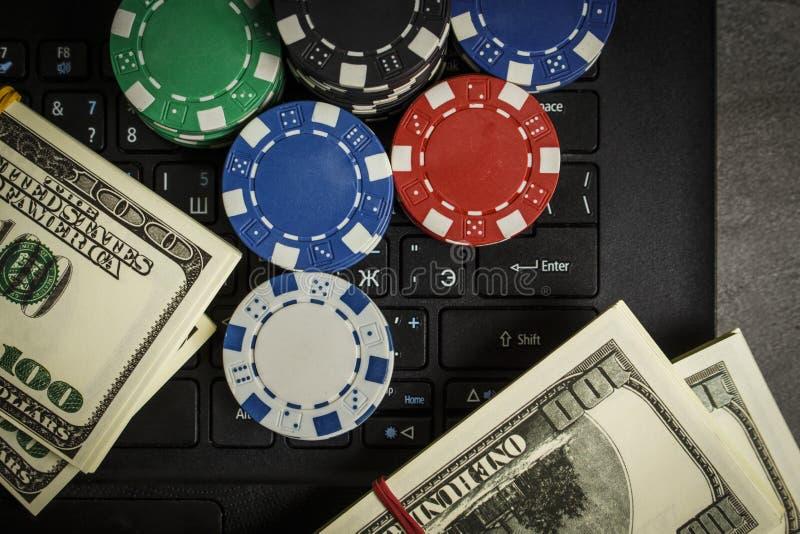 Обломоки покера и пакеты долларов на ноутбуке стоковые изображения