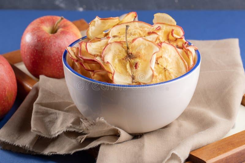 Обломоки яблока конца-вверх в чашке и свежие яблоки на бежевой ткани н стоковые изображения