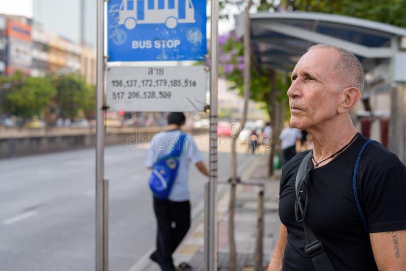 Облыселый старший туристский человек думая пока ждущ на автобусной остановке i стоковое фото