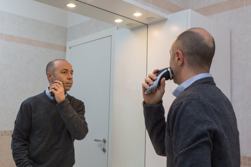 Облыселый человек при рубашка и свитер брея его бороду с электробритвой и зеркалом стоковое фото rf
