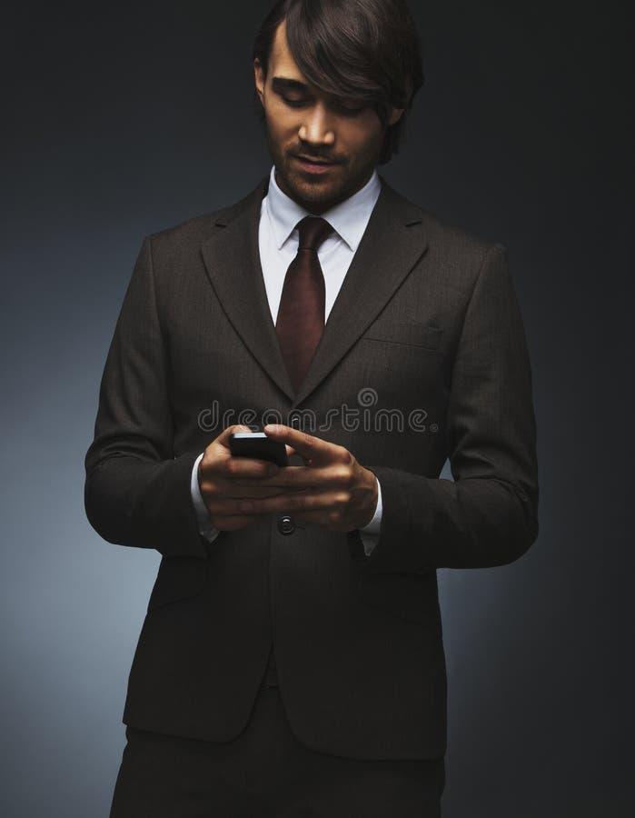 Обмен текстовыми сообщениями бизнесмена на его smartphone стоковое изображение rf