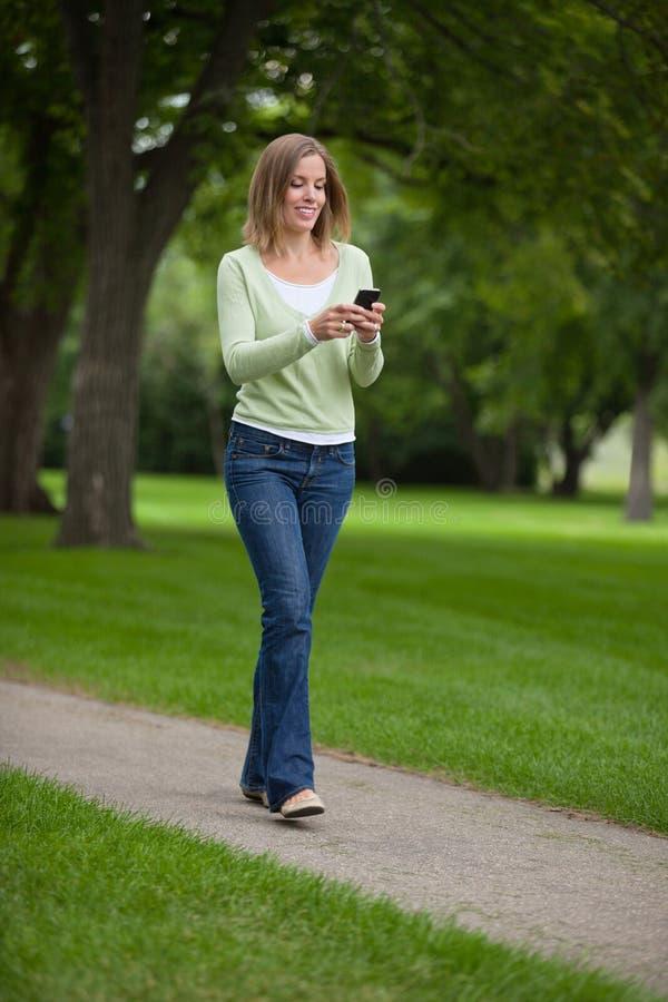 Обмен текстовыми сообщениями женщины в парке стоковые изображения rf