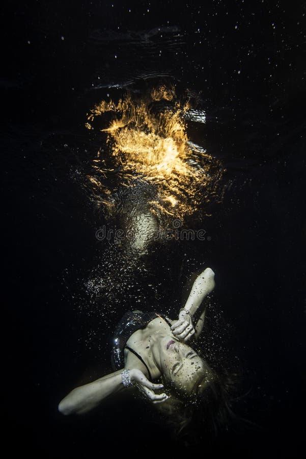 Обморочные lavitates девушки подводные над поверхностью с огнем стоковые фото