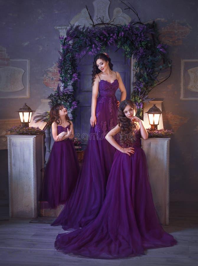 Обмундирование семьи Мама и 2 дочери представляя против фона blossoming двора в великолепном пурпуре стоковое фото