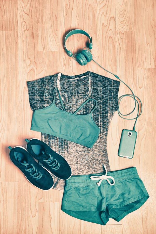 Обмундирование фитнеса одежд спортзала Соответствуя одежда для девушки тренируя дома с наушниками и телефоном для того чтобы слуш стоковое фото