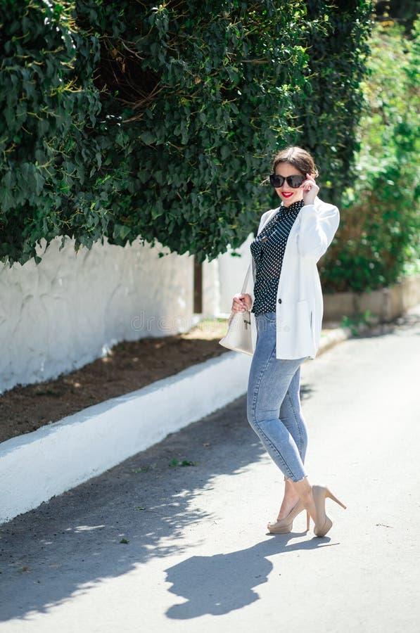Обмундирование whilte моды ультрамодной красивой смеясь женщины в солнечных очках представляя на белой предпосылке стены стоковая фотография rf