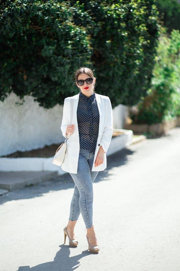 Обмундирование whilte моды ультрамодной красивой смеясь женщины в солнечных очках представляя на белой предпосылке стены стоковые фото