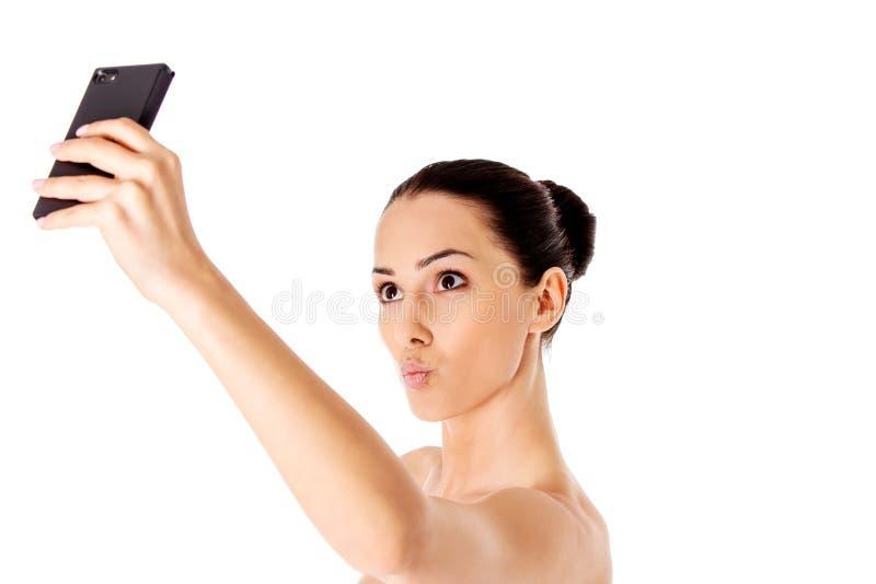 Обнажённая красивая женщина принимая selfie на белой предпосылке стоковая фотография rf