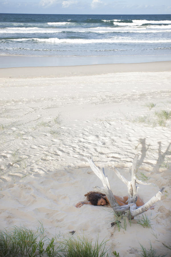 Обнажённая молодая дама спать в песке на пляже стоковое фото