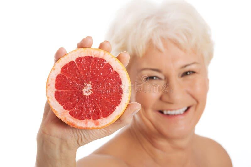 Обнажённая старуха держа грейпфрут. стоковые изображения