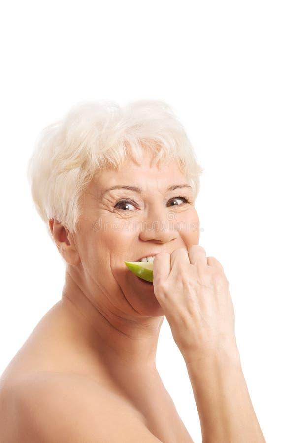 Обнажённая старуха есть яблоко. стоковое фото rf