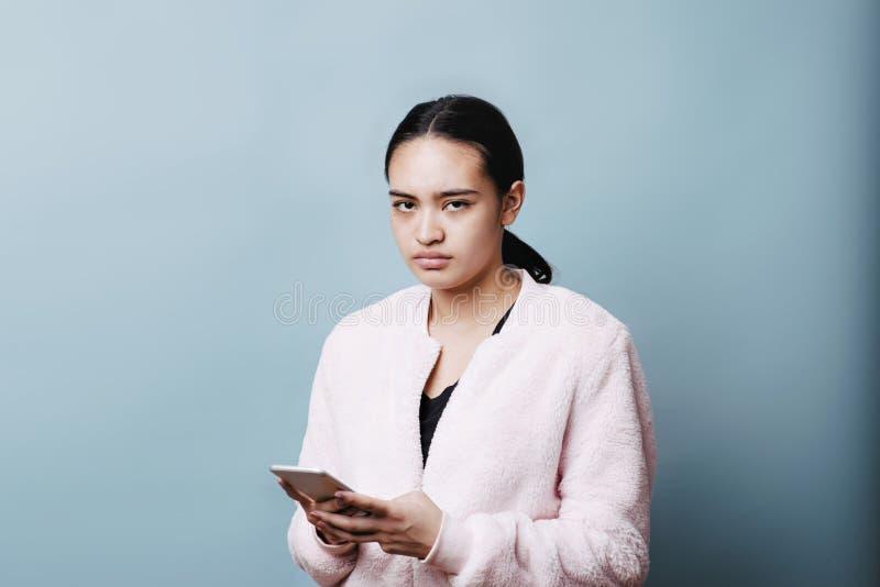 Обнесенное решеткой место в суде девочка-подростка знонит по телефону и имеет сердитому выражению на ее стороне стоковое изображение