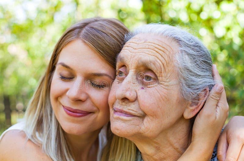 Обнимать бабушку в парке стоковые фотографии rf