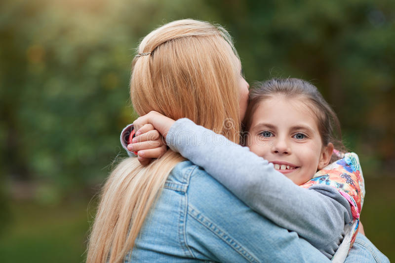 Обнимать ее мать в парке стоковое фото rf