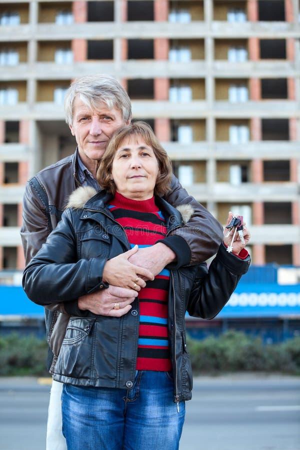 Обнимать любящих старших пар с ключом дома в руке стоковое фото