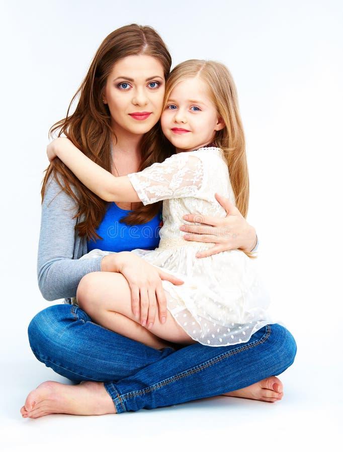 Обнимающ мать и дочь изолированные на белой предпосылке стоковые изображения